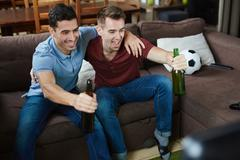 Guys with beer cheering up in front of tv screen Stock Photos