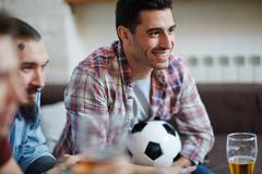 Group of friendly guys spending leisure together in front of tv Stock Photos