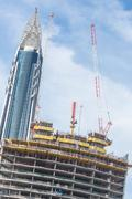 Skyscrappers construction site with cranes on top of buildings Stock Photos