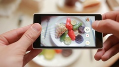 Trendy man in a restaurant make photo of food with mobile phone camera Stock Footage