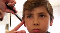 Child having a haircut. Cutting hair of young boy at hairdresser. Kid getting a  Stock Footage