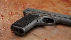 Pistol in blood close-up Stock Footage