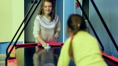 Beautiful young girl enthusiastically playing air hockey in the room Stock Footage