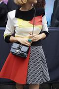 Woman in applique top, A line skirt and handbag, mid section Stock Photos