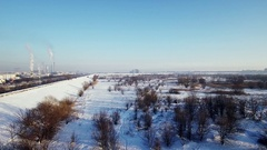 Aerial view of natural park covered in snow with skyline of city Stock Footage