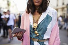 Woman in pink coat and necklace holds phone in street, crop Stock Photos