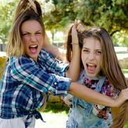 Angry girlfriends fighting pulling long hair Stock Photos