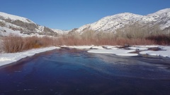 Aerial mountain valley winter ice snow river pond 4K Stock Footage