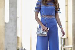 Woman in blue jumpsuit with white handbag, horizontal crop Stock Photos
