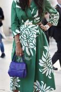 Woman in green wrap-over dress with purple bag, vertical crop Stock Photos
