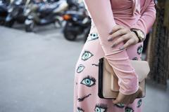 Woman wearing pink top and eye print skirt, mid section Stock Photos