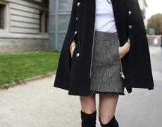 Woman in street wearing tweed miniskirt and black cape, crop Stock Photos