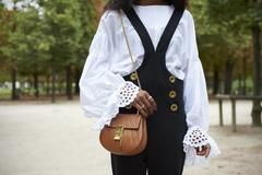 Woman in dungarees and a gypsy blouse in park, mid section Stock Photos