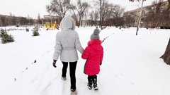 Two girls, mother and daughter, walking at a park in winter frosty day. Stock Footage