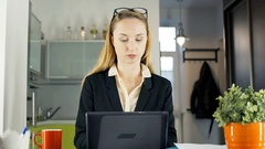 Businesswoman working on papers and adding water from boiling pot to the coffee Stock Footage