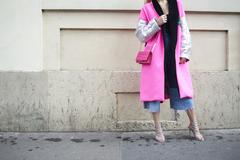 Woman in pink and silver coat holding pink bag, crop Stock Photos