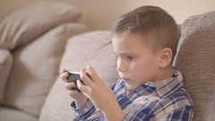 Side view of young boy playing with smart phone on couch Stock Footage
