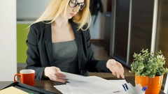 Businesswoman working on papers and answers cellphone, steadycam shot Stock Footage