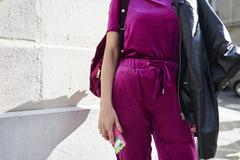 Woman in magenta top and track pants in street, mid section Stock Photos
