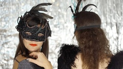 Woman in carnival mask turning to the camera while her friend is standing back Stock Footage