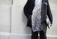Woman in black suit and sequinned silver tunic, mid section Stock Photos