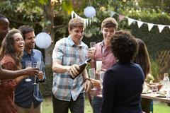 Gay Couple Celebrating With Champagne At Outdoor Backyard Party Stock Photos