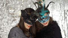 Beautiful women in carnival masks doing photo on smartphone, steadycam shot Stock Footage