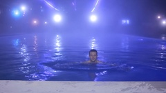 Happy man Swim in the pool at night and drinking from glasses. Thermal source Stock Footage