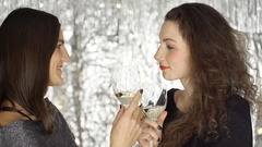 Two, beautiful women holding glasses with champagne and chatting, steadycam shot Stock Footage