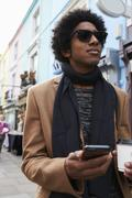 Young Man Using Phone On Busy City Street Stock Photos