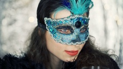 Woman in carnival mask fluttering herself with fan and drinking champagne Stock Footage