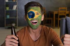 Happy man with painted flag of Brazil Kuvituskuvat