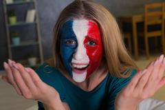 Diisappointed woman with painted flag of France Kuvituskuvat