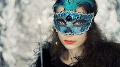 Woman in carnival mask holding sparkler and doing serious look to the camera Stock Footage