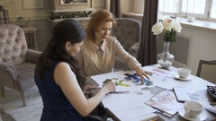 Clother designers woman creates a sketch on the paper to her client in tailor Stock Footage