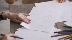 Clother designers woman creates a sketch on the paper closeup in tailor studio Stock Footage