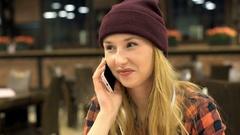 Happy, hipster girl chatting on cellphone in the cafe, steadycam shot Stock Footage