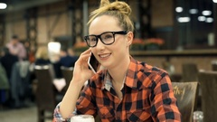 Happy girl in checked shirt sitting in the cafe and chatting on cellphone Stock Footage