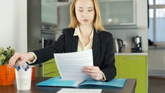 Businesswoman sitting in the apartment and working on papers, steadycam shot Stock Footage
