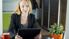 Happy businesswoman sitting at the table and having a videocall on tablet, stead Stock Footage