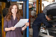 Female Customer In Auto Repair Shop Satisfied With Bill For Car Repair Stock Photos