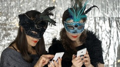 Women in carnival masks using smartphones at the masquerade party, steadycam  Stock Footage