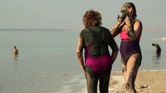 Mud therapy, women stands on the beach and rubs mud on the body from Dead Sea Stock Footage