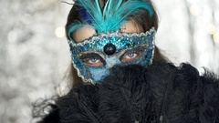 Woman in carnival mask hiding behind black fan and looking to the camera, steady Stock Footage