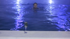 Woman at night in the pool with thermal water with a glass of champagne Stock Footage
