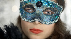 Woman in carnival mask holding fan and looking to the camera, steadycam shot Stock Footage