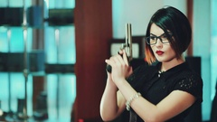 Girl brunette in glasses with black frames, aim at a target holding a gun Stock Footage