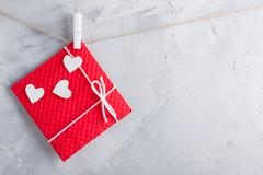 Red gift card wih paper hearts on gray concrete background. Stock Photos