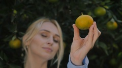 Young woman demonstrate an orange in close-up near a green trees Stock Footage