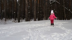 Girl child is learning to ski. She slowly slides on skis in soft fresh snow. Stock Footage